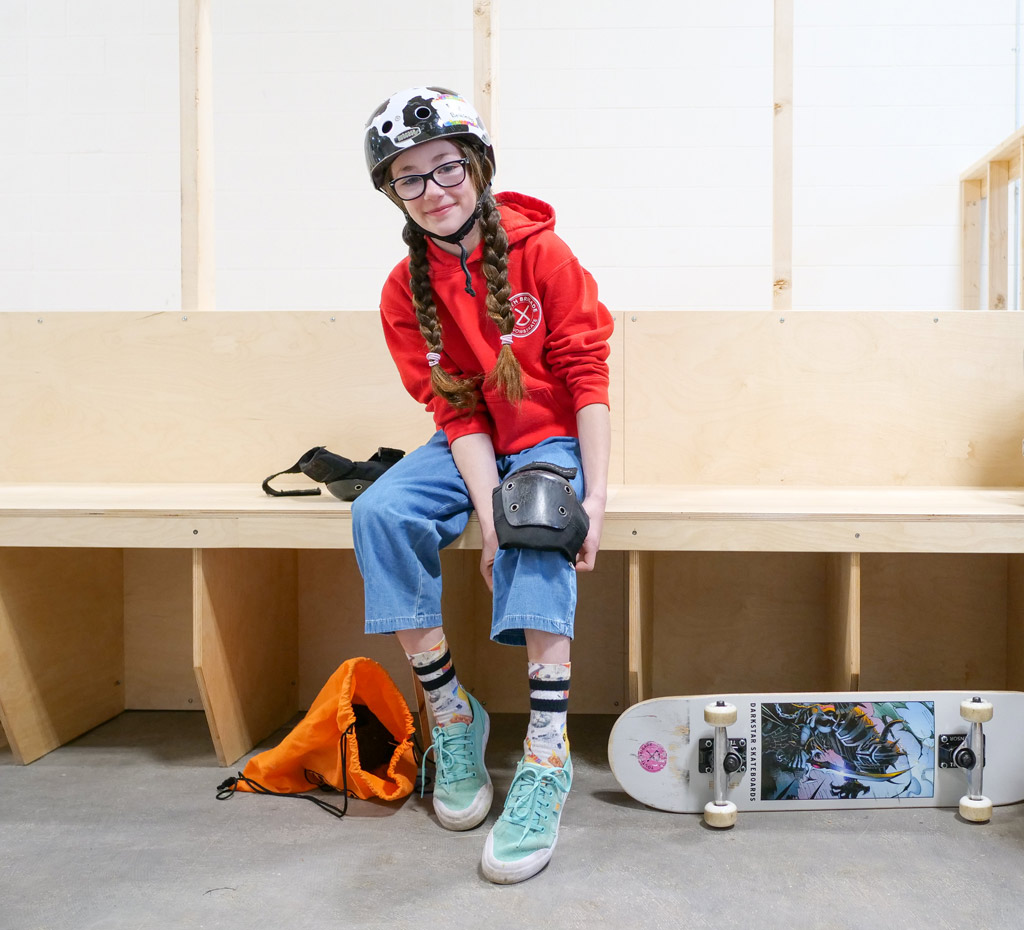 young skateboard girl at getting geared up at the park