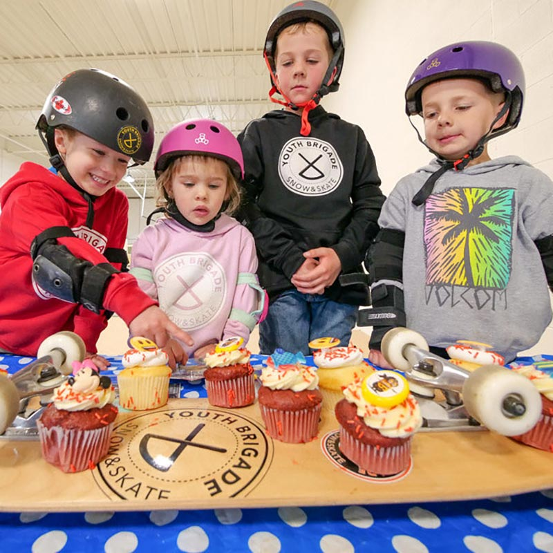 skater kids with birthday cupcakes at the park